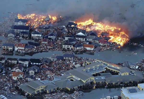 An aerial view shows houses burning and the Natori river flooded over the surrounding area in Natori city, Miyagi Prefecture, March 11, 2011. 8.8 magnitude earthquake strikes in Tohoku area,, northern part of Japan, bringing tsunami, a huge tidal wave covering Kesennuma port, Miyagi and Miyako port Iwate Prefecture.( The Yomiuri Shimbun via AP Images )
